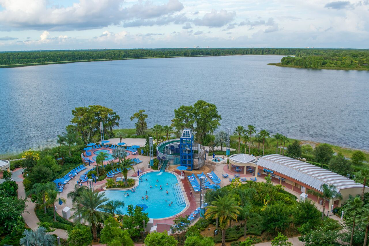 A waterslide feeds into the pool at Bay Lake Tower, surrounded by a lake