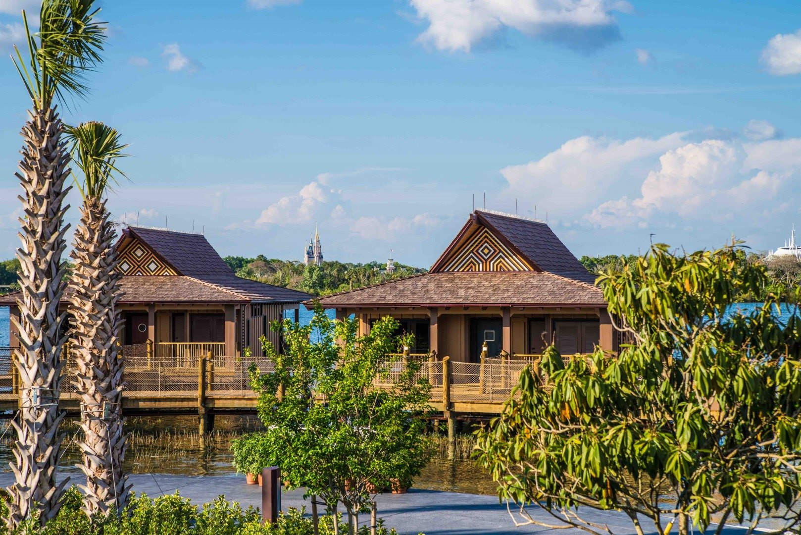Cinderella's Castle can be spotted in the distance behind two bungalows at Disney's Polynesian Resort