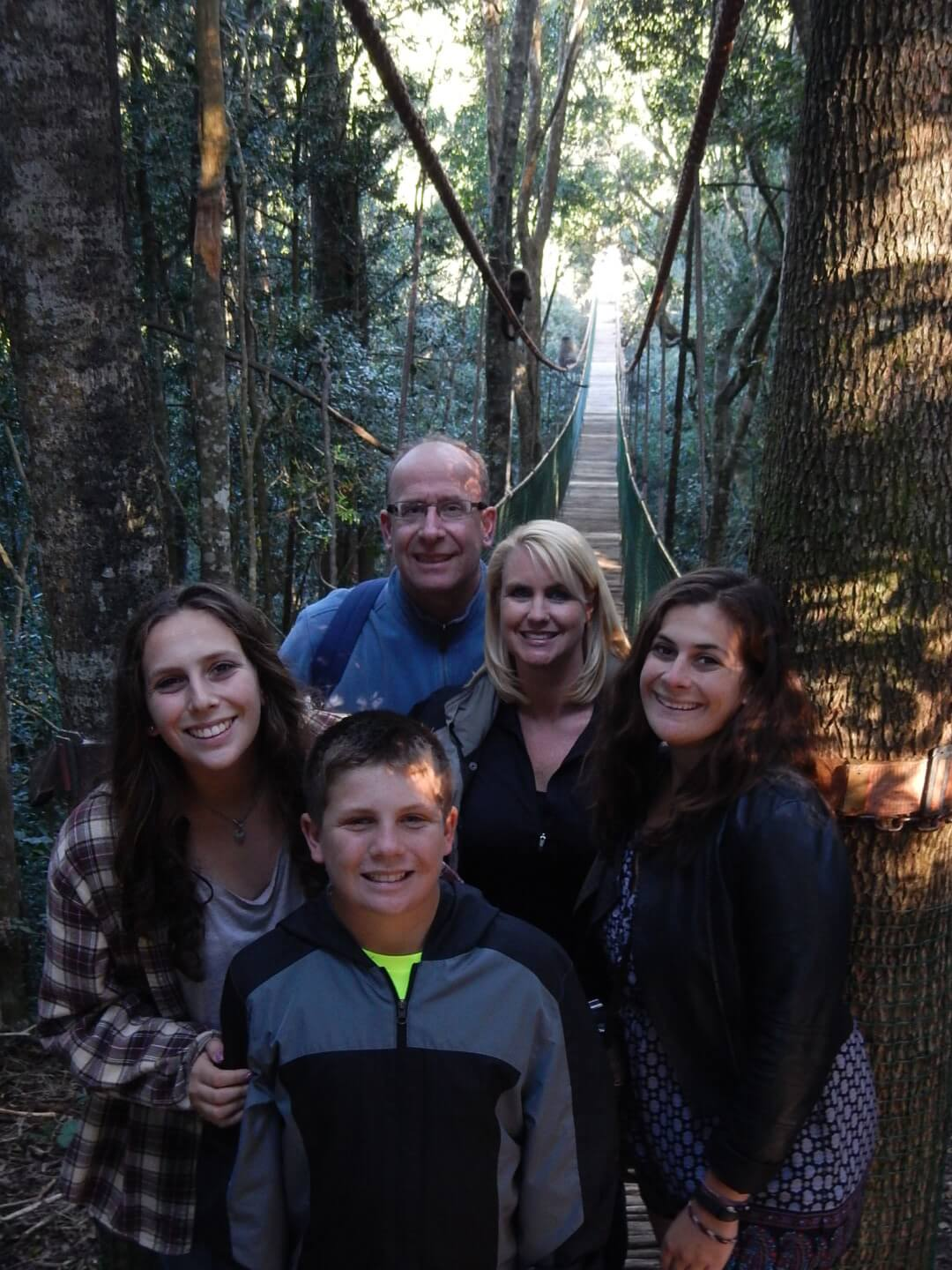 Andy Berry and family posing for a picture on a rope bridge in a forest.