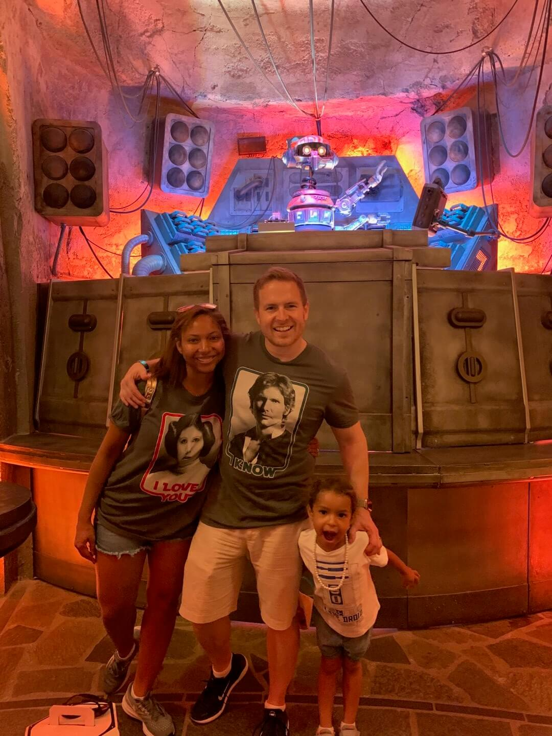 Happy family posing in front of Disney's Galaxy's Edge Star Wars droid.