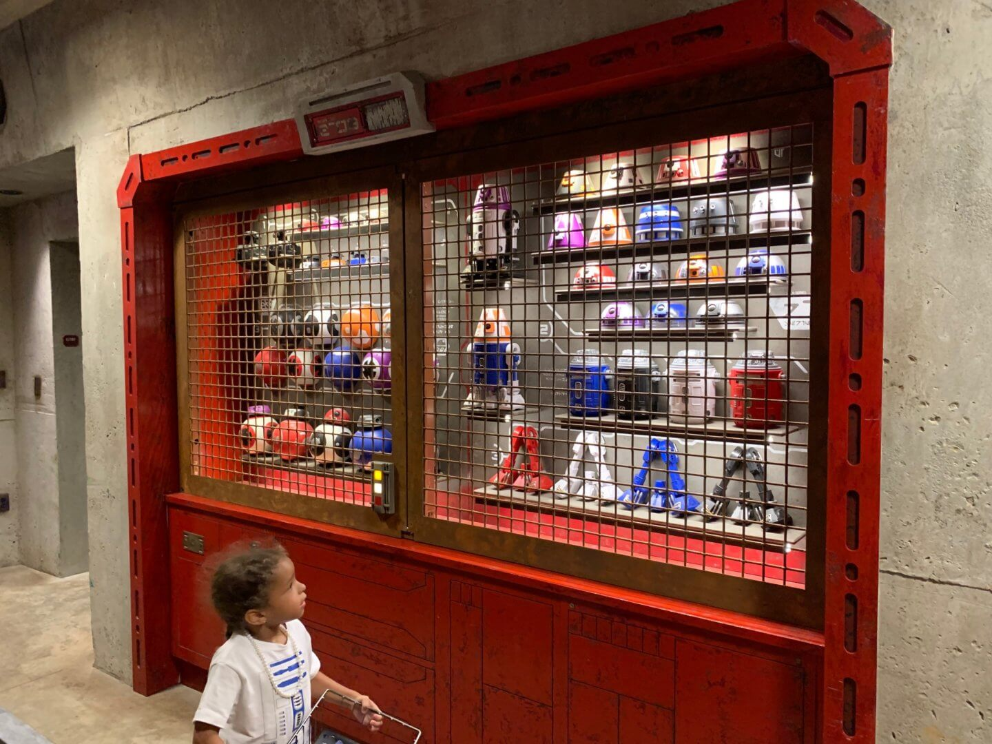 Little girl looking at selection of droid parts at Disney's Galaxy's Edge Star Wars park.