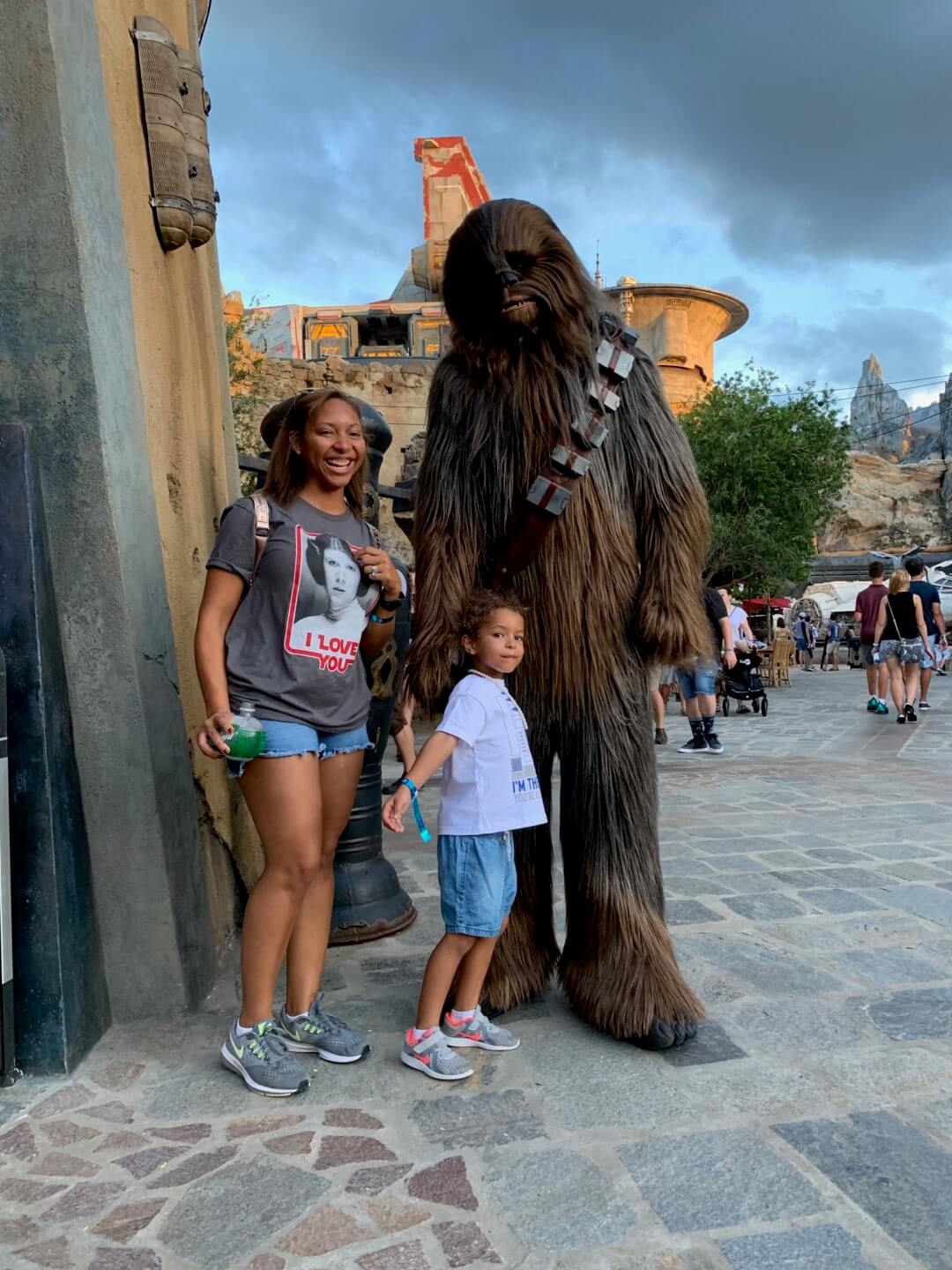 Chewbacca at Disney's Galaxy's Edge posing with mother and daughter